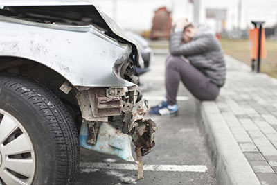 Warsaw Auto Accident Attorney - Person sitting on the side of the road next to his vehicle that has been in an accident