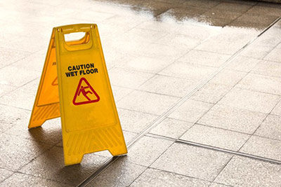Warsaw Slip and Fall Lawyer - Photo of a wet floor with a caution wet floor sign on the ground