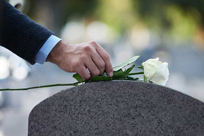 Warsaw Wrongful Death Lawyers - Photo of a persons hand placing a rose on a head stone